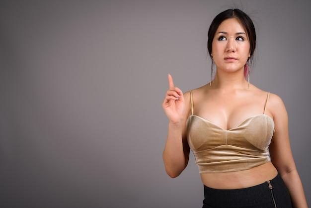 Jonge mooie aziatische vrouw tegen grijze muur