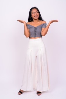 Jonge mooie aziatische vrouw tegen witte muur