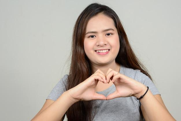 Jonge mooie aziatische vrouw tegen witte ruimte