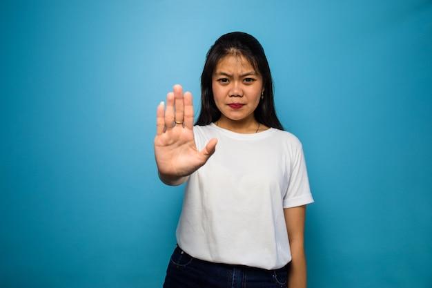 Jonge mooie aziatische vrouwen die een wit t-shirt met een blauwe geïsoleerde achtergrond gebruiken, weigeren gebaar