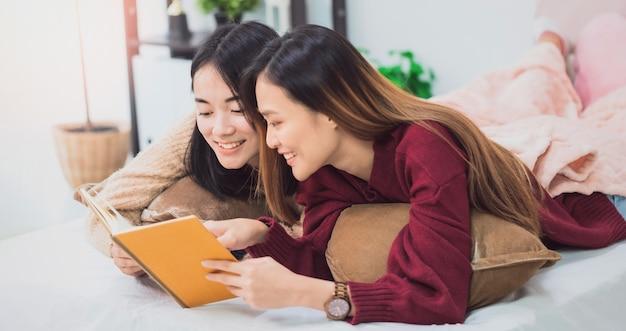 Jonge mooie aziatische vrouwen lesbisch koppel minnaar leesboek in woonkamer thuis.