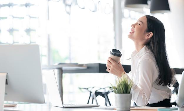 Jonge mooie aziatische zakenvrouw die een kopje koffie vasthoudt en glimlacht tijdens het werk op kantoor.