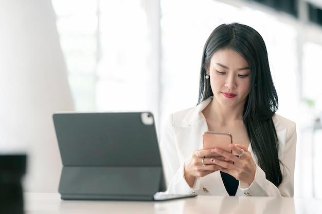Jonge mooie aziatische zakenvrouw die smartphone gebruikt terwijl ze aan haar bureau zit.