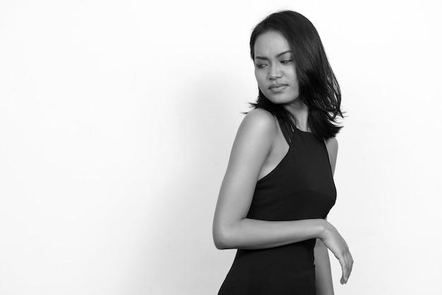 Jonge mooie aziatische zakenvrouw draagt jurk tegen witte muur in zwart en wit