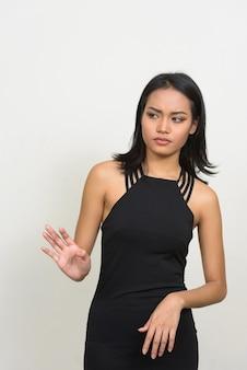 Jonge mooie aziatische zakenvrouw draagt jurk tegen witte muur