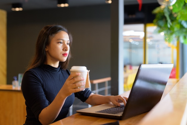 Jonge mooie aziatische zakenvrouw koffie drinken tijdens het gebruik van laptop in de koffieshop
