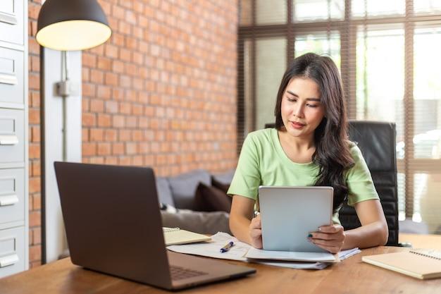 Jonge mooie aziatische zakenvrouw met behulp van een computertablet tijdens het werken vanuit haar kantoor aan huis tijdens covid pandamic lockdown