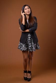 Jonge mooie aziatische zakenvrouw tegen bruine achtergrond