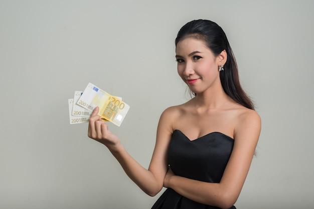 Jonge mooie aziatische zakenvrouw tegen witte ruimte