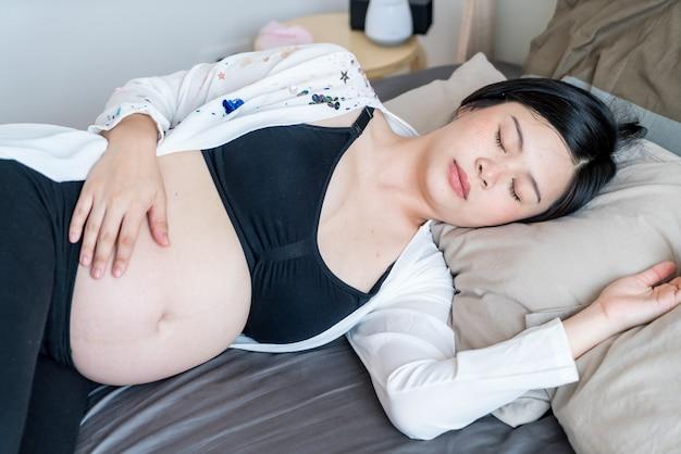 Jonge mooie aziatische zwangere vrouwenslaap op bed
