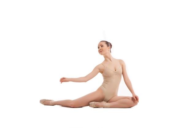 Jonge mooie balletdanser zittend in elegante pose geïsoleerd op wit