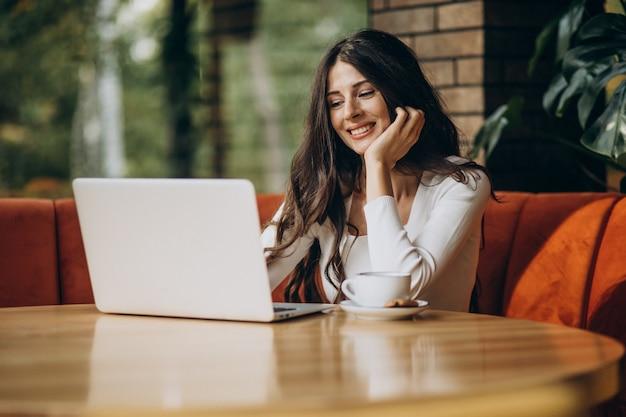 Jonge mooie bedrijfsvrouw die aan computer in een koffie werkt