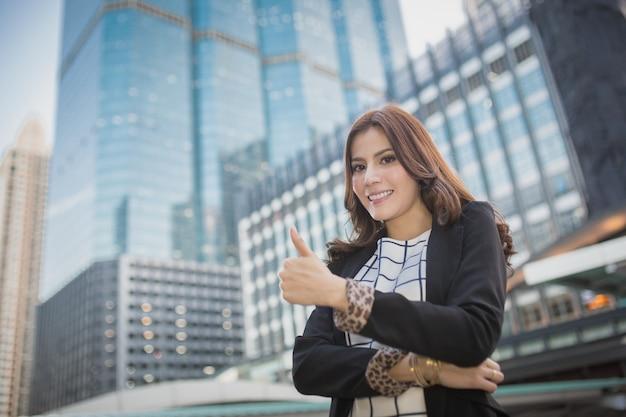 Jonge mooie bedrijfsvrouw die duim op hand, bedrijfsconcept succes toont