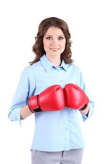 Jonge mooie bedrijfsvrouw met bokshandschoenen die op wit wordt geïsoleerd