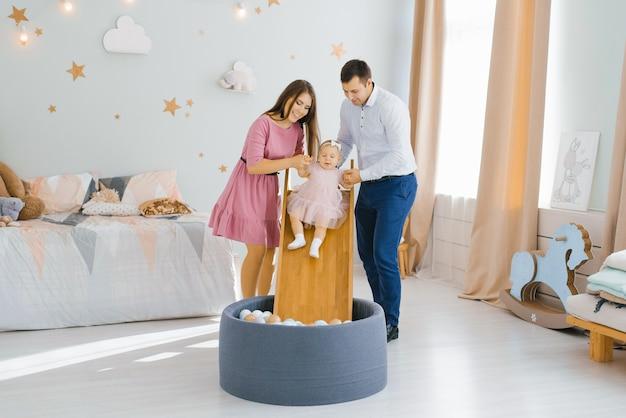 Jonge mooie blanke familie spelen met hun eenjarige dochter in de kinderkamer.