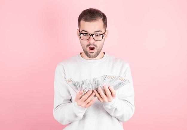 Jonge mooie blanke man geschokt door het winnen van de loterij. de man kijkt naar het pakje geld dat ze heeft gewonnen.