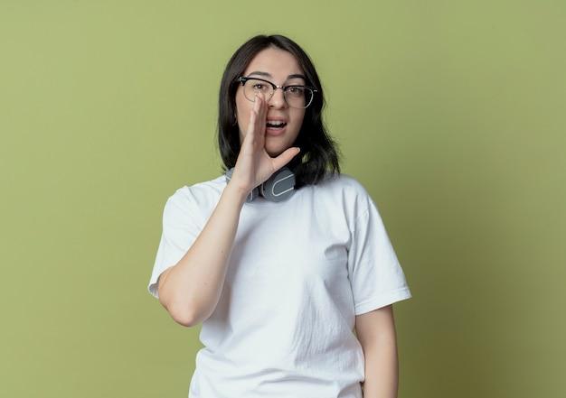 Jonge, mooie blanke meid met een bril en koptelefoon op de nek die iets fluistert en kijkt