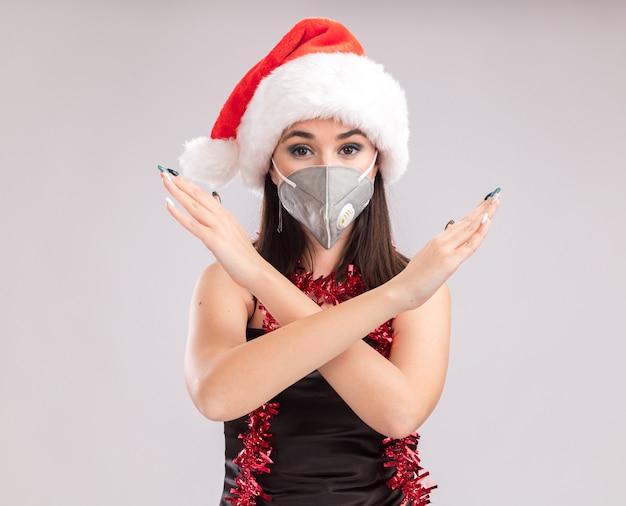 Jonge mooie blanke meisje dragen kerstmuts en beschermende masker klatergoud slinger rond nek kijken camera doen geen gebaar geïsoleerd op witte achtergrond