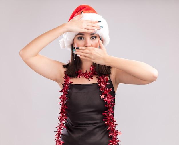 Jonge mooie blanke meisje dragen kerstmuts en klatergoud slinger rond nek houden hand op mond en voorhoofd kijken camera geïsoleerd op witte achtergrond