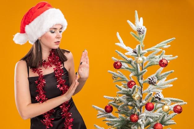 Jonge mooie blanke meisje met kerstmuts en klatergoud slinger rond nek staande in de buurt van versierde kerstboom kijken naar het doen weigering gebaar geïsoleerd op een oranje achtergrond