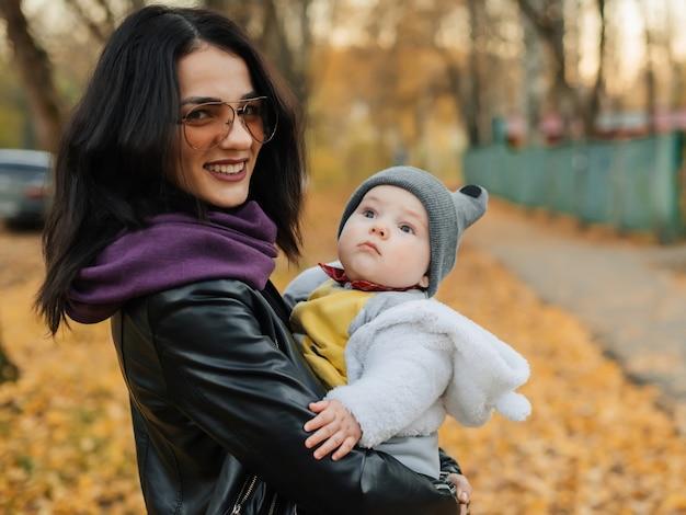 Jonge mooie blanke meisje moeder lacht en houdt haar zoontje