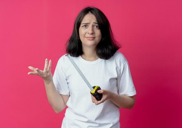 Jonge mooie blanke meisje tape meter houden en lege hand tonen geïsoleerd op karmozijnrode achtergrond met kopie ruimte verward