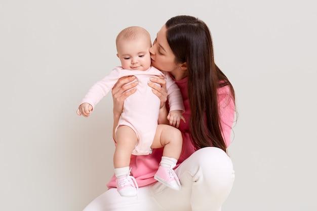 Jonge mooie blanke moeder met lang donker haar poseren met pasgeboren baby baby jurken romper en sokken. wijfje dat vrijetijdskleding draagt, die op witte muur wordt geïsoleerd.