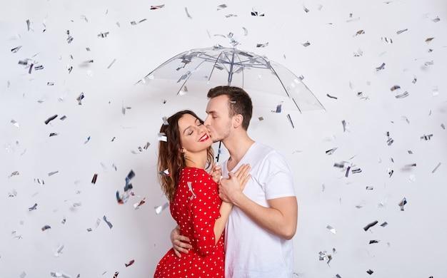 Jonge mooie blanke paar onder een paraplu van vallende confetti.