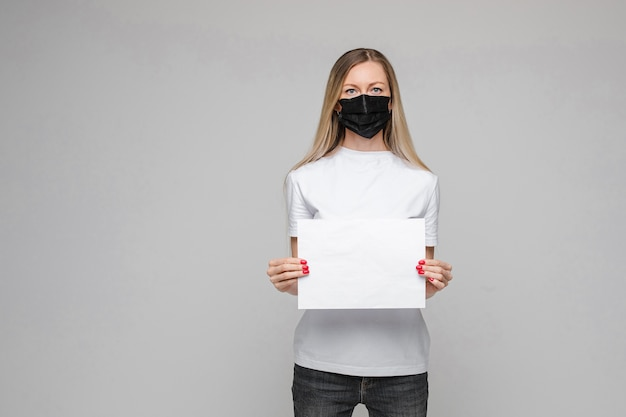 Jonge mooie blanke tiener in wit t-shirt, spijkerbroek staat met zwarte medische masker houdt witte broadsheet