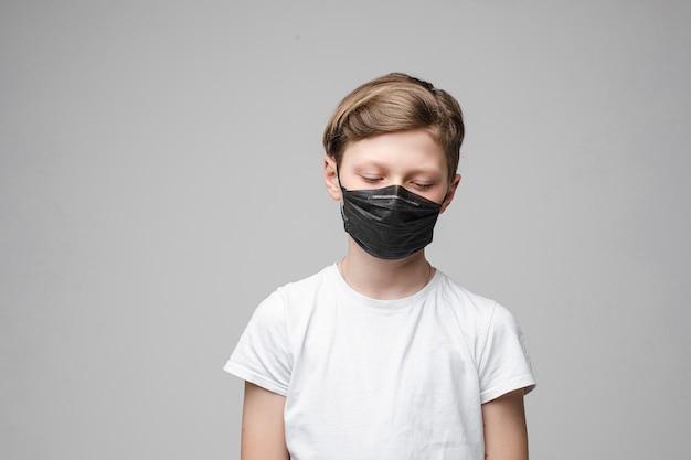 Jonge mooie blanke tiener in wit t-shirt, zwarte spijkerbroek staat met zwarte medische masker neerkijkt