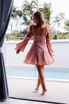 Jonge mooie blanke vrouw alleen in schattige zomerjurk op vakantie in luxevilla