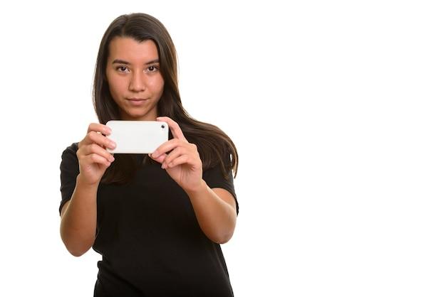 Jonge mooie blanke vrouw die foto met mobiele telefoon op wit wordt geïsoleerd