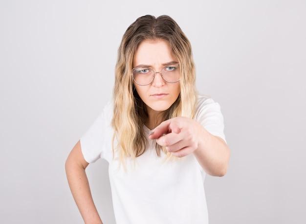 Jonge mooie blanke vrouw die ontevreden en gefrustreerd naar de camera wijst