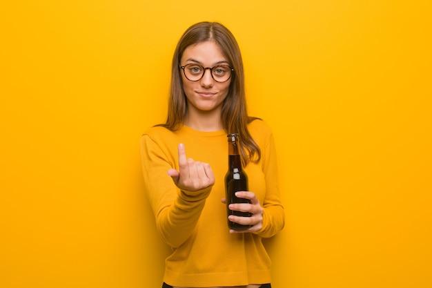 Jonge mooie blanke vrouw die uitnodigt om te komen. ze houdt een biertje vast.