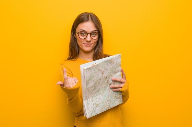 Jonge mooie blanke vrouw die uitnodigt om te komen. ze houdt een kaart vast.