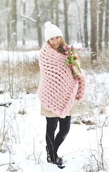 Jonge mooie blanke vrouw in winterkleren en gigantische breien pastel roze deken met lentebloemen wandelen in het besneeuwde bos dromen over lente witte hoed