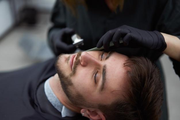 Jonge mooie blanke vrouw kapper snijdt baard knappe man bij moderne kapperszaak
