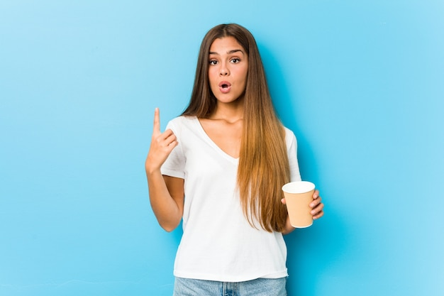 Jonge mooie blanke vrouw met een afhaalkoffie met een geweldig idee, concept van creativiteit.