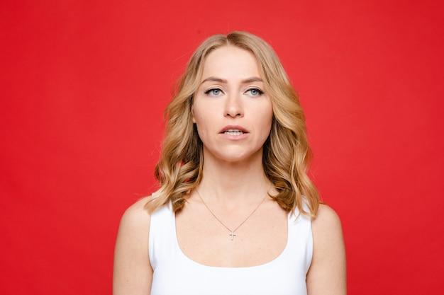 Jonge mooie blanke vrouw met halflang blond golvend haar en naakt make-up in wit t-shirt is saai, foto geïsoleerd op rode achtergrond