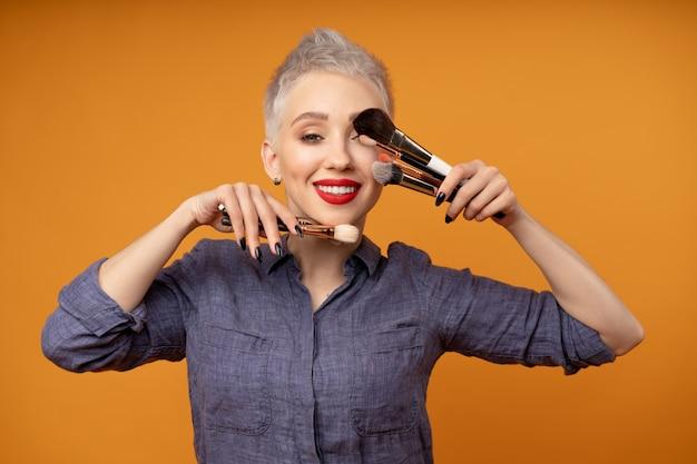 Jonge mooie blanke vrouw met kort haar bedrijf make-up borstels