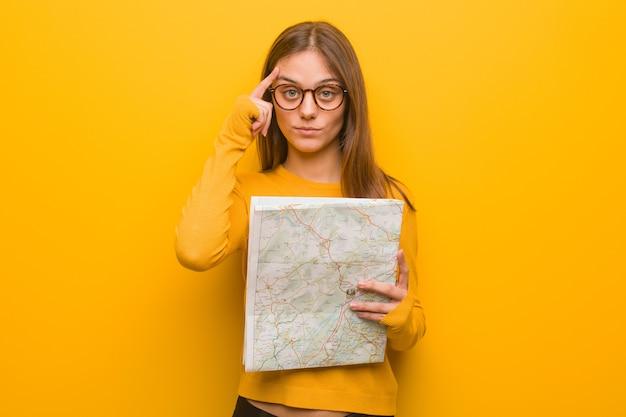 Jonge mooie blanke vrouw na te denken over een idee. ze houdt een kaart vast.