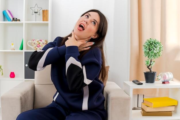 Jonge mooie blanke vrouw zittend op een fauteuil in de ontworpen woonkamer beu opzoeken en zichzelf stikken