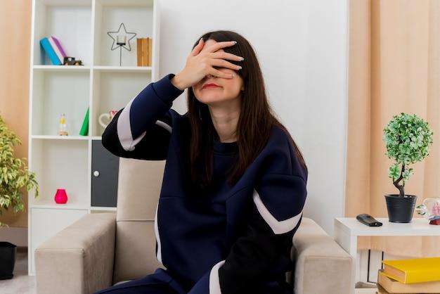 Jonge mooie blanke vrouw zittend op een fauteuil in ontworpen woonkamer hand op gezicht bedekkende ogen zetten