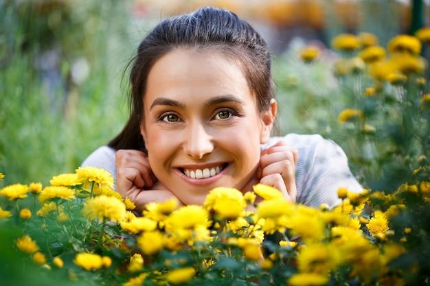 Jonge mooie bloemist poseren, glimlachend onder bloemen.