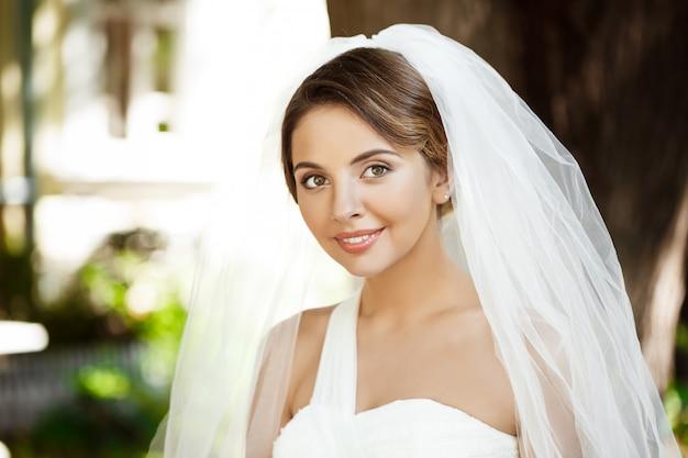 Jonge mooie blonde bruid in trouwjurk en sluier glimlachen.