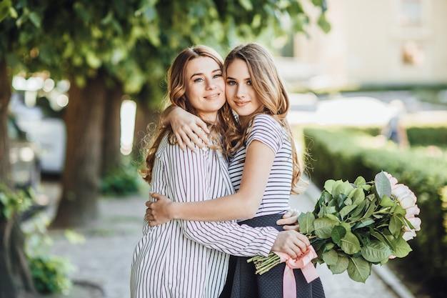 Jonge mooie blonde dochter omhelst haar moeder van middelbare leeftijd in de straten van de stad. ze zijn gelukkig en houden van elkaar.