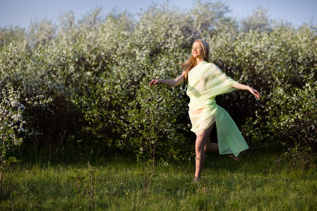Jonge mooie blonde glimlachende vrouw die in gele transparante doek op gras over de bloeiende achtergrond van kersenbomen springt