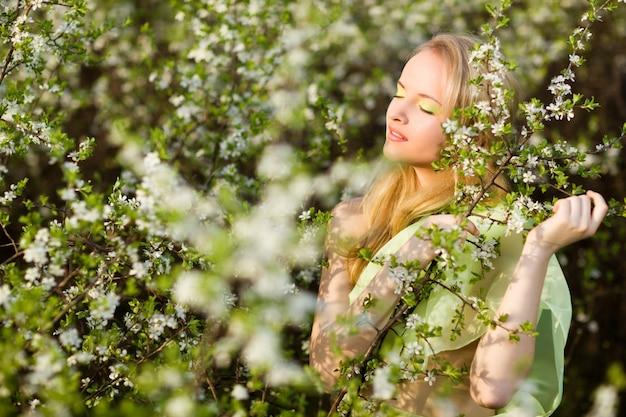Jonge mooie blonde glimlachende vrouw in gele kleding die zich in bloeiende kersenbomen bevindt en bloem bekijkt