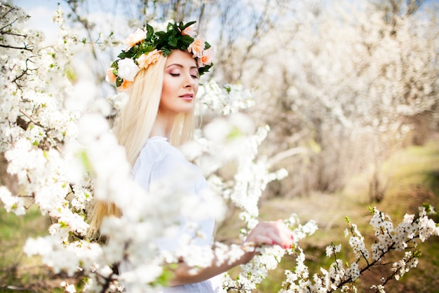 Jonge mooie blonde glimlachende vrouw in witte minikleding die zich met bloeiende bomen bij achtergrond bevinden