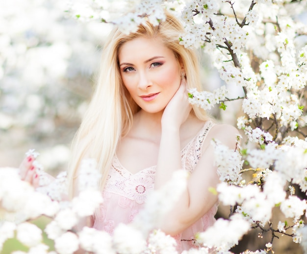 Jonge mooie blonde glimlachende vrouw in witte minikleding